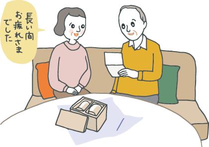 退職した男性が、退職祝いのプレゼントを前に、自宅でメッセージカードを読んでいるところに、奥さんが「長い間おつかれさまでした」と声をかけている。